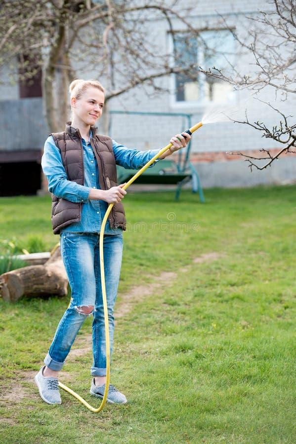 美丽的少妇浇灌的草坪在一晴朗的美好的天  库存照片