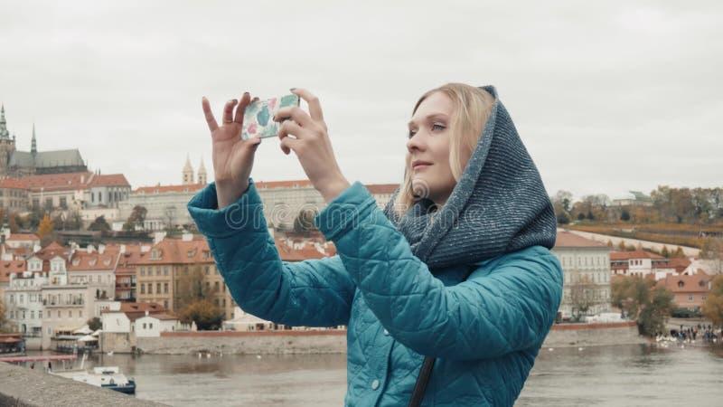 美丽的少妇游人在布拉格,做Selfie或拍与她的手机的照片,旅行的概念 库存照片