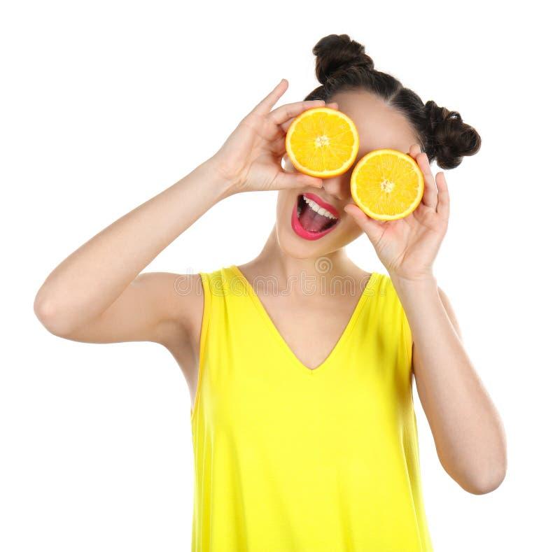 美丽的少妇用桔子在眼睛附近对分 免版税库存照片
