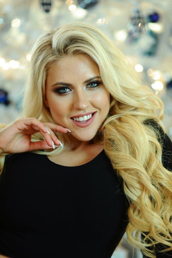 美丽的少妇画象有卷曲金发和魅力构成的 免版税库存图片