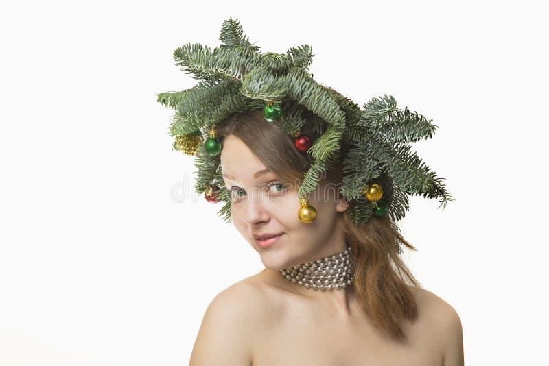 美丽的少妇画象有圣诞节花圈的在whi 图库摄影