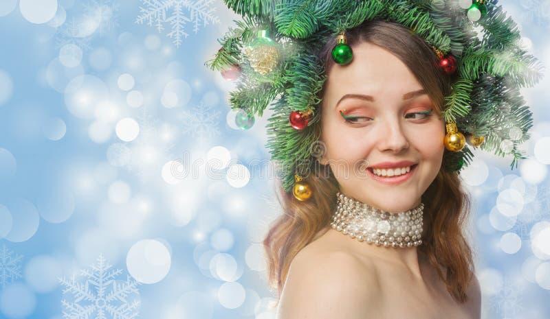 美丽的少妇画象有圣诞节花圈的 免版税库存图片