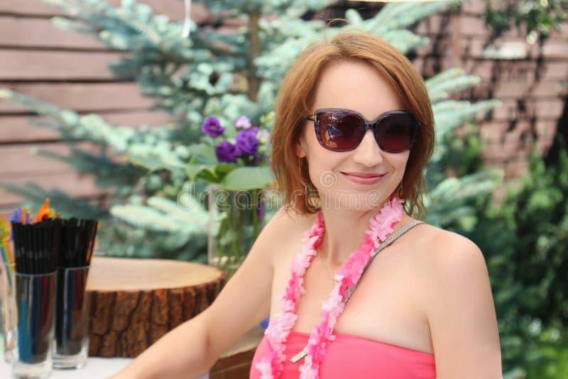 美丽的少妇画象泳装的拿着桑格里酒鸡尾酒和获得在室外池边聚会的乐趣在后院 免版税库存图片