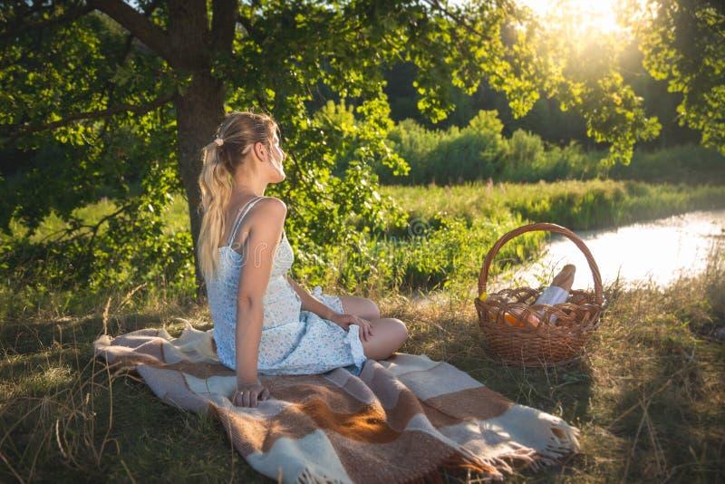 美丽的少妇的被定调子的图象有野餐在看在湖的大树下晚上太阳 免版税图库摄影