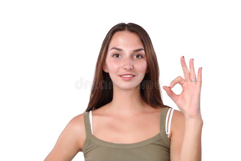美丽的少妇看照相机,显示好标志和微笑,站立对灰色墙壁 库存照片
