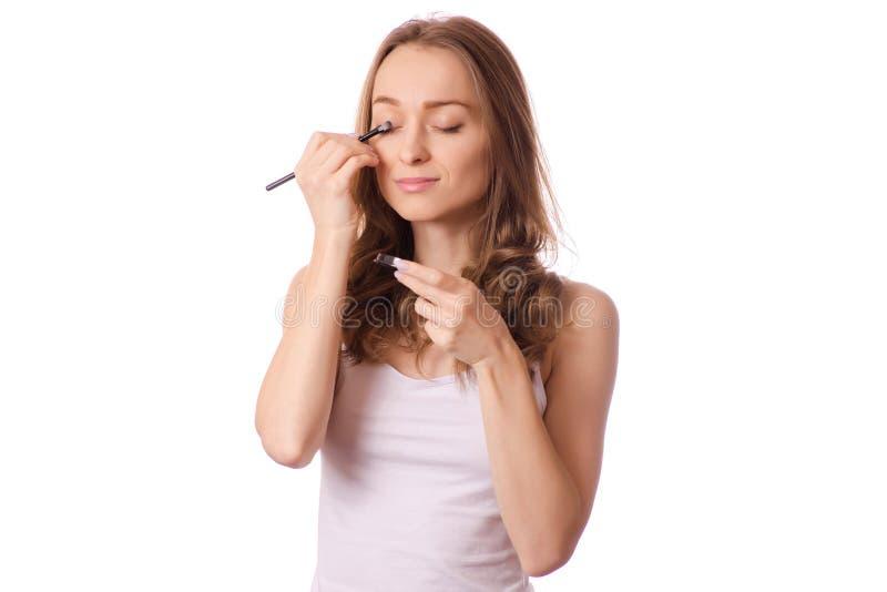 美丽的少妇眼影和构成刷子 免版税库存图片