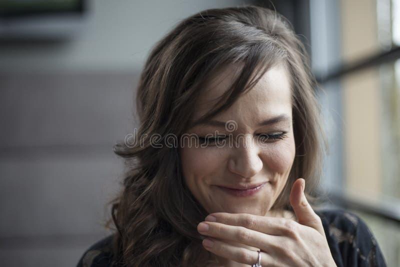 美丽的少妇纵向有布朗头发笑的 库存照片
