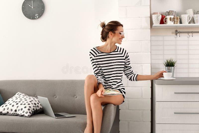 美丽的少妇读书杂志和饮用的茶在家 免版税库存照片