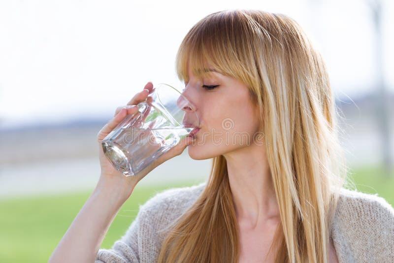 美丽的少妇饮用水玻璃在公园 免版税库存图片
