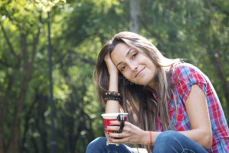 美丽的少妇饮用的咖啡在早晨公园 库存图片