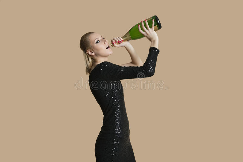 美丽的少妇饮用的香槟画象从瓶的在色的背景 免版税库存图片