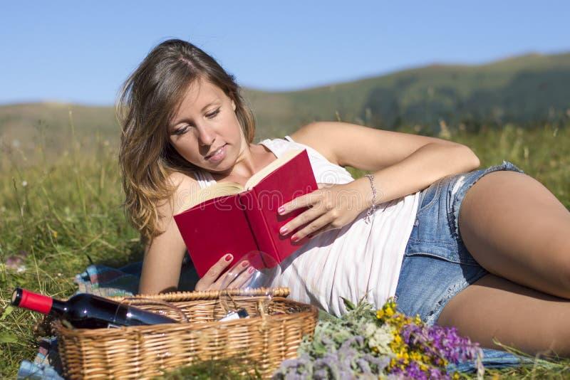 美丽的少妇说谎在草甸的,阅读书,在p旁边 库存照片