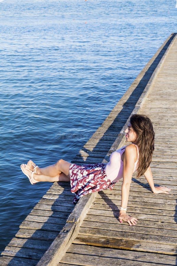 美丽的少妇画象坐一个木码头 免版税库存照片