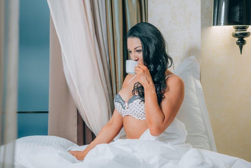 美丽的少妇画象拿着在床上的睡衣的咖啡杯 免版税库存照片