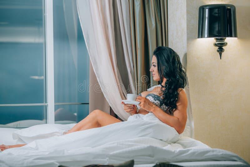 美丽的少妇画象拿着在床上的睡衣的咖啡杯 免版税图库摄影