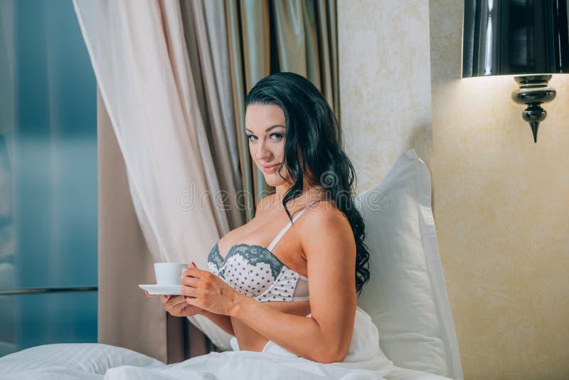 美丽的少妇画象拿着在床上的睡衣的咖啡杯 图库摄影
