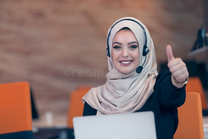 美丽的工作在起始的办公室的电话操作员阿拉伯妇女 免版税库存照片