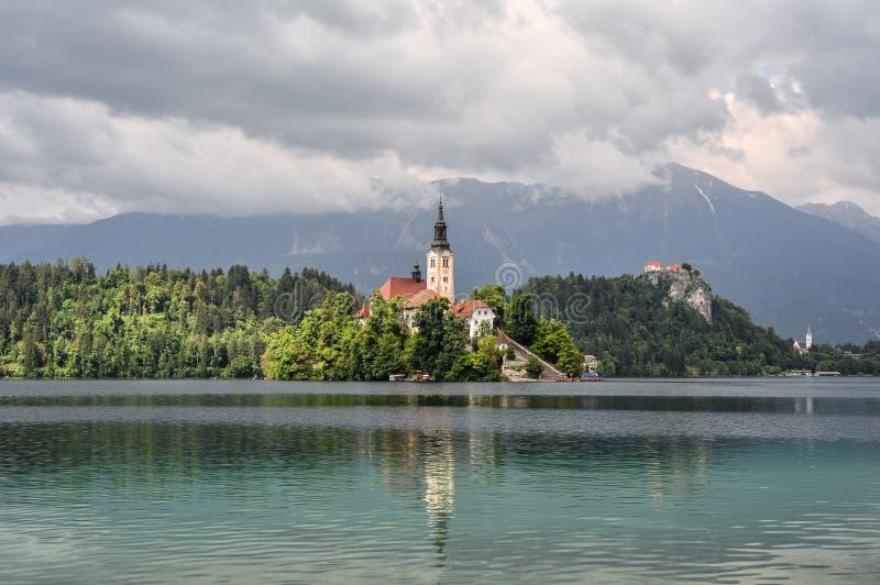 美丽的布莱德湖在朱利安阿尔卑斯山和圣母升天节教会,流血的斯洛文尼亚 山,在中间的老教会 库存图片