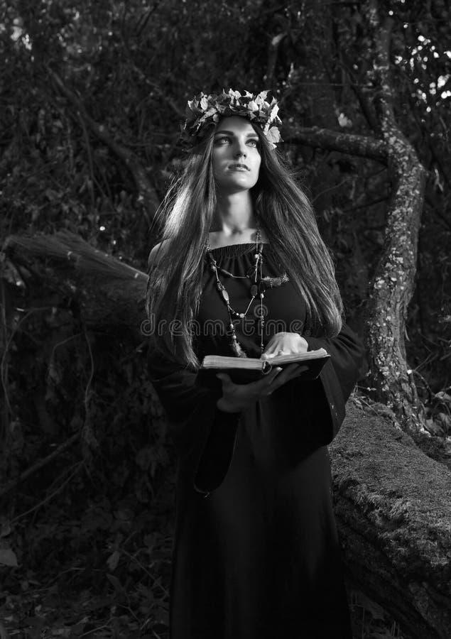 美丽的年轻万圣节巫婆佩带的葡萄酒哥特式礼服和 免版税库存图片