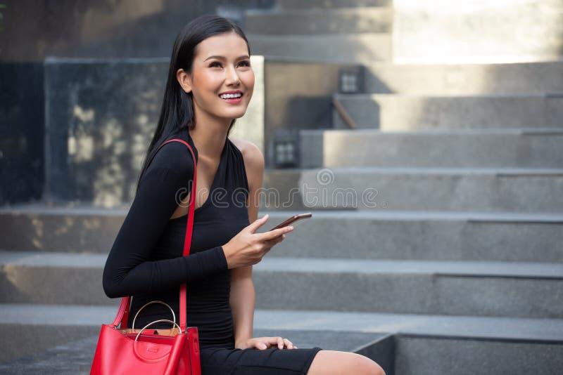 美丽的年轻亚裔女商人画象黑礼服的叫与坐在城市的智能手机 愉快的典雅的夫人 免版税库存图片