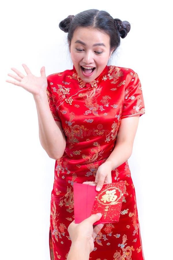 美丽的年轻亚裔妇女佩带的汉语穿戴传统cheongsam 被接受的红色信封 惊奇和愉快的微笑 图库摄影