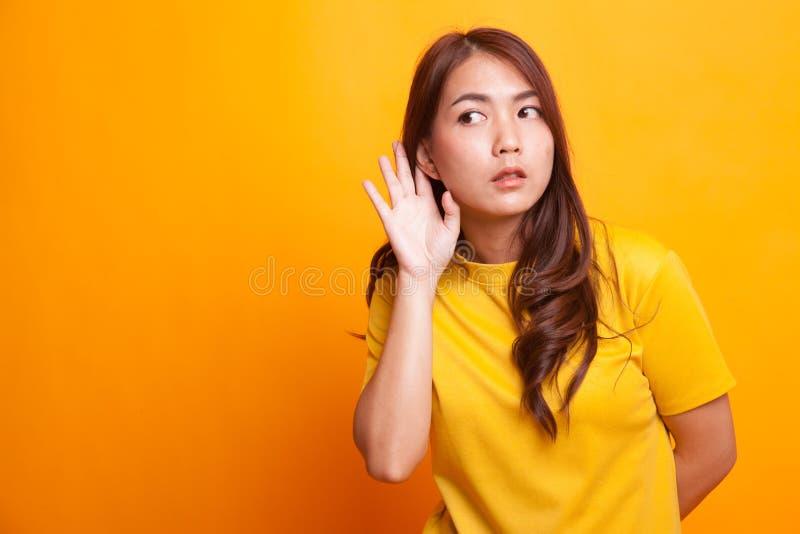 美丽的年轻亚裔妇女听某事 免版税库存照片