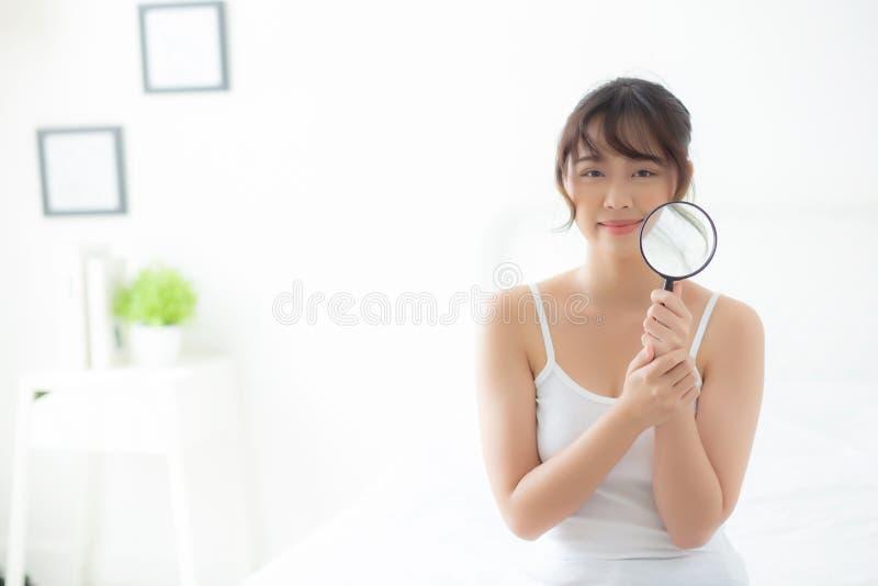美丽的年轻亚裔妇女满意对粉刺,面孔秀丽亚洲女孩微笑的检查skincare扩大化的皮肤  免版税图库摄影