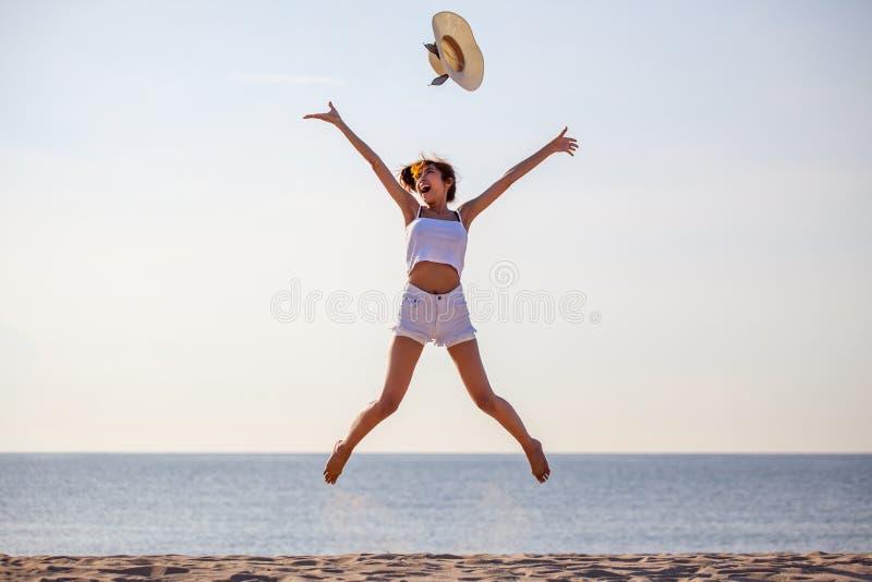 美丽的年轻亚裔妇女激动的投掷的帽子在海海滩的空气 愉快的女孩享受假日假期 库存图片