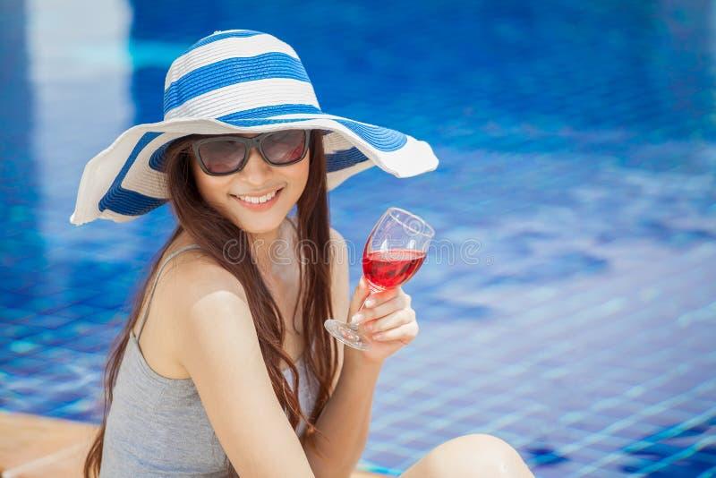美丽的年轻亚裔妇女用在夏天党的饮料在游泳场附近 大帽子和玻璃放松的愉快的女孩 库存图片
