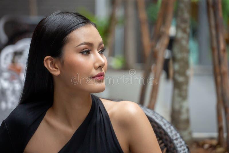 美丽的年轻亚裔妇女画象看在城市的一件黑礼服的室外 免版税库存图片