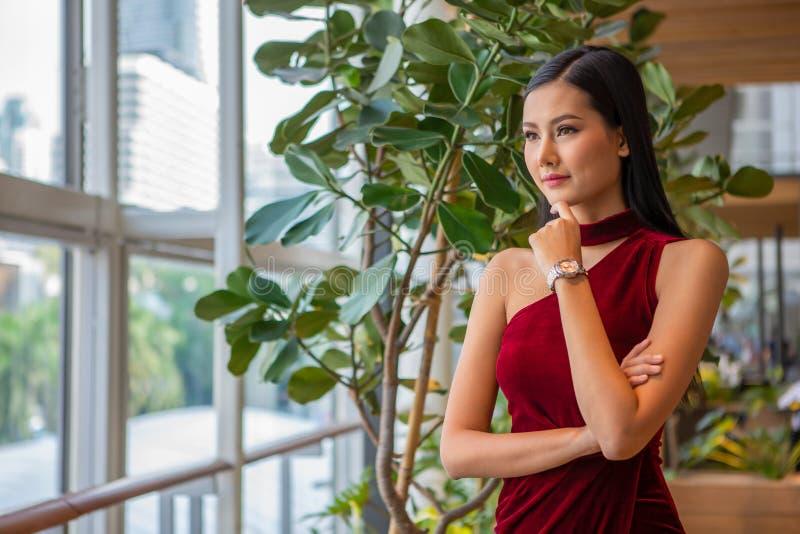 美丽的年轻亚裔妇女画象站立和看窗口的红色礼服的 典雅的夫人模型正面认为 库存图片