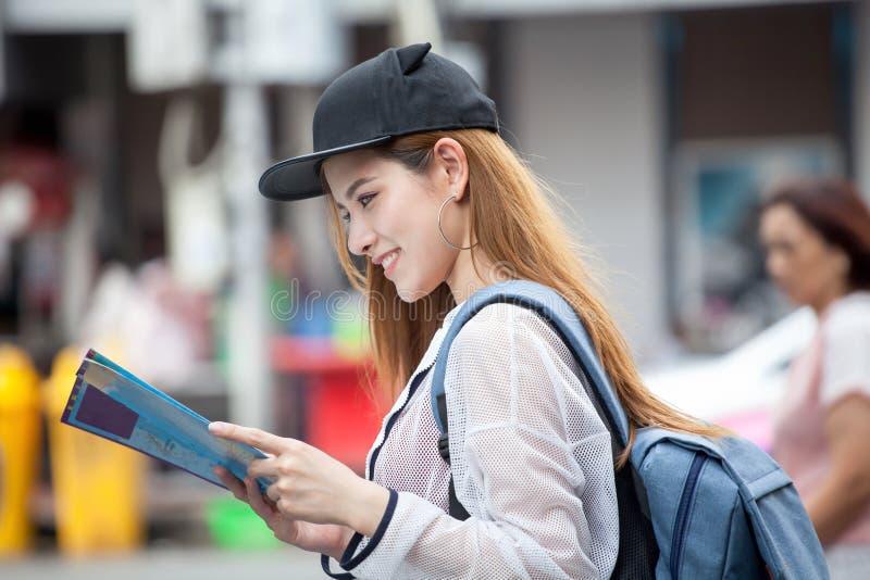 美丽的年轻亚裔微笑与backpa的妇女旅游旅客 库存图片