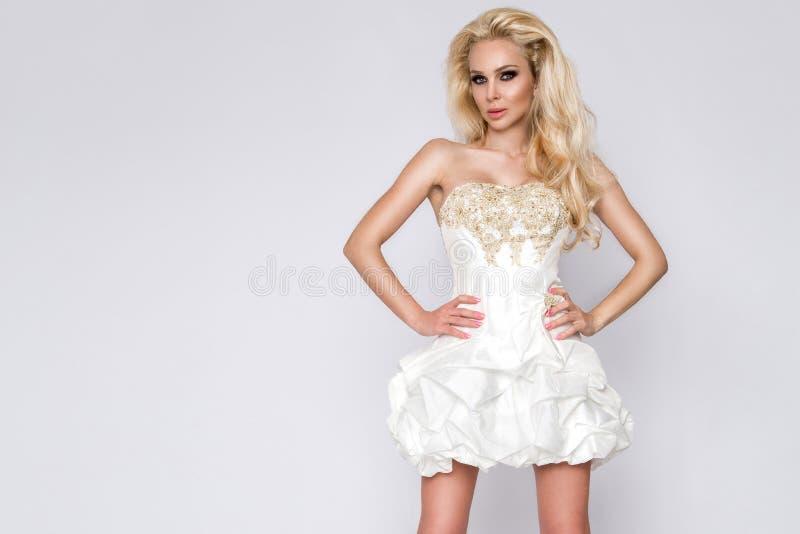 美丽的年轻人,性感的匀称白肤金发的妇女,有卷曲长的头发模型的一位公主,白色长的惊人的婚礼礼服的新娘 免版税库存图片