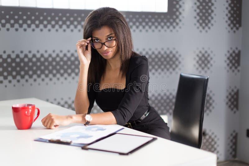 美丽的年轻企业夫人在黑强的随员坐在办公室桌上 图库摄影