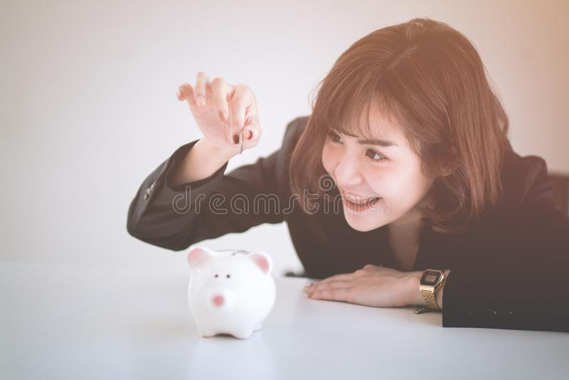 美丽的年轻企业女孩挽救金钱 免版税图库摄影