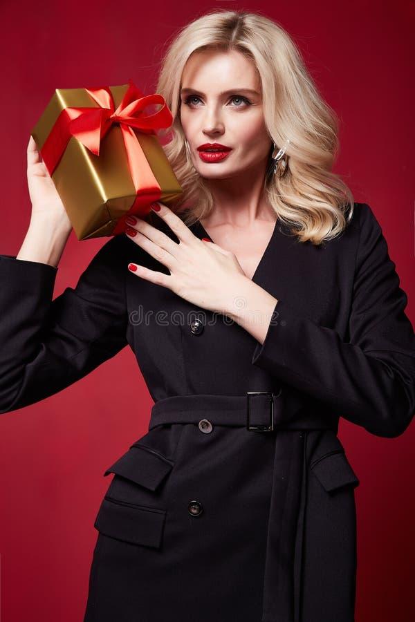 美丽的年轻俏丽的发光的红色口红妇女明亮的平衡的构成在嘴唇白肤金发的卷发欢乐心情被编织的冬天 免版税库存图片