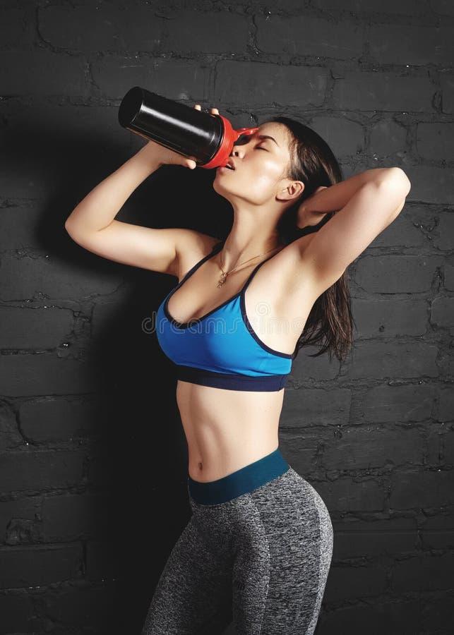 美丽的年轻健身妇女以时尚炫耀衣裳 女孩举行体育营养振动器 与性感的身体的健身模型 免版税库存照片