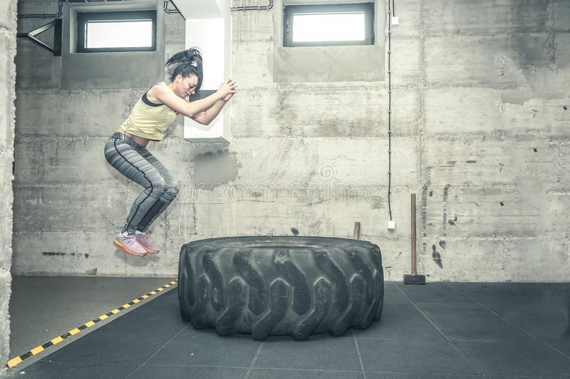 美丽的年轻和可爱的健身女孩在拖拉机轮胎跳作为在健身房的坚硬与影片五谷的锻炼,图象和行动 免版税库存照片