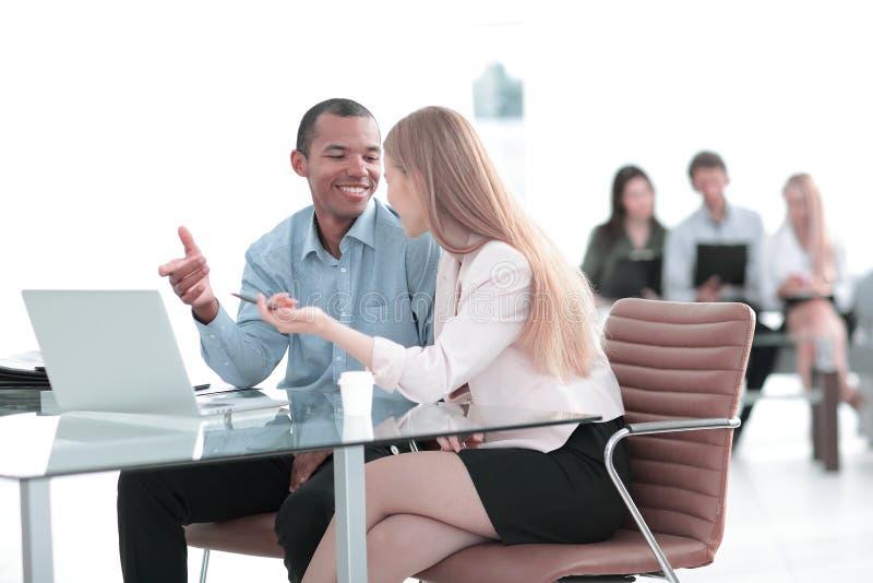 美丽的年轻商务伙伴使用一台膝上型计算机,谈论文件 免版税库存照片