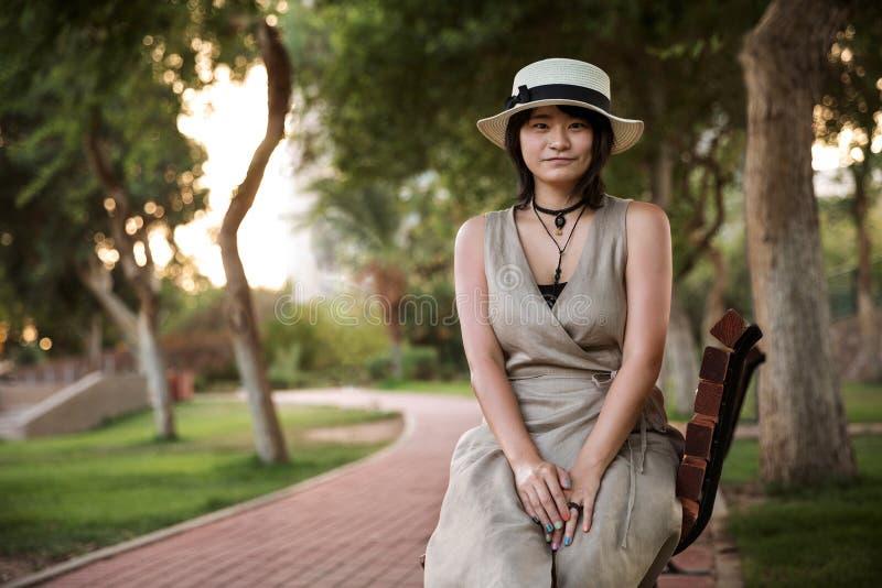 美丽的年轻坐在公园的学生亚裔女孩 免版税图库摄影