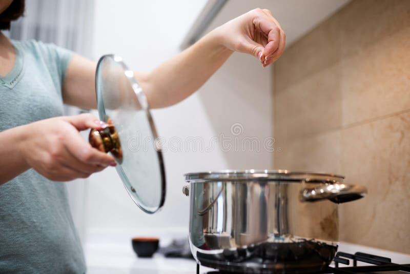 美丽的年轻女人主妇prepairing的晚餐,在大钢平底深锅的倾吐的盐,站立在气体火炉 库存图片