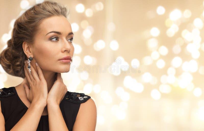 美丽的年轻女人佩带的金刚石耳环 免版税库存图片