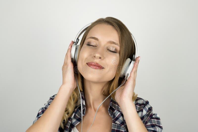美丽的年轻女人听的音乐在耳机被隔绝的白色背景中 免版税库存图片