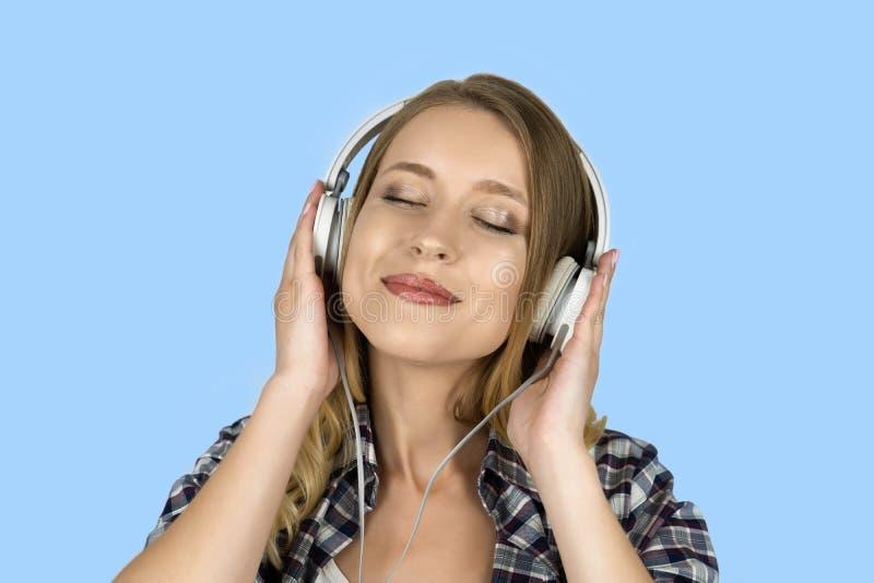 美丽的年轻女人听的音乐在耳机被隔绝的蓝色背景中 库存照片