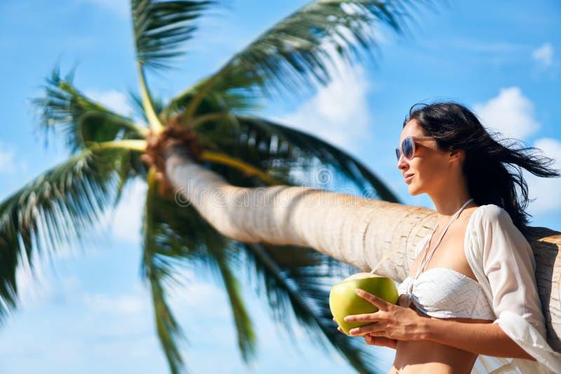 美丽的年轻女人在与棕榈树的热带海滩享受椰子饮料并且放松 免版税库存图片