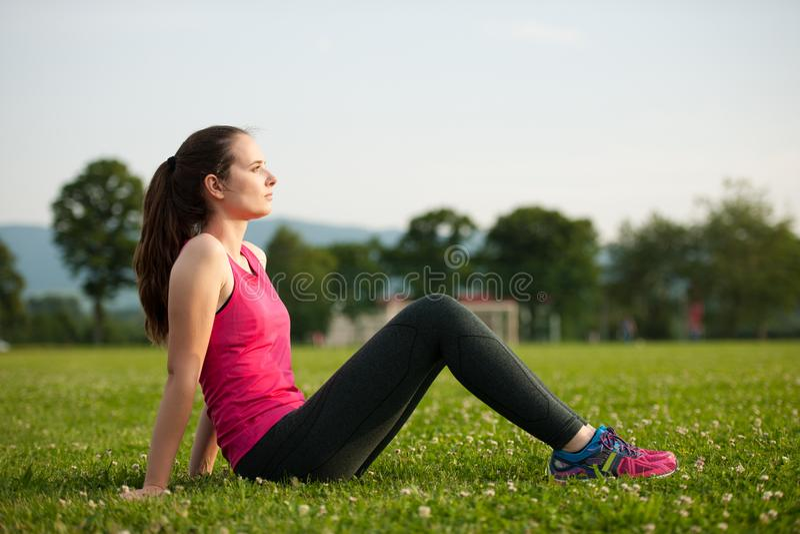 美丽的年轻女人在室外一种历时长久的锻炼以后休息  库存图片