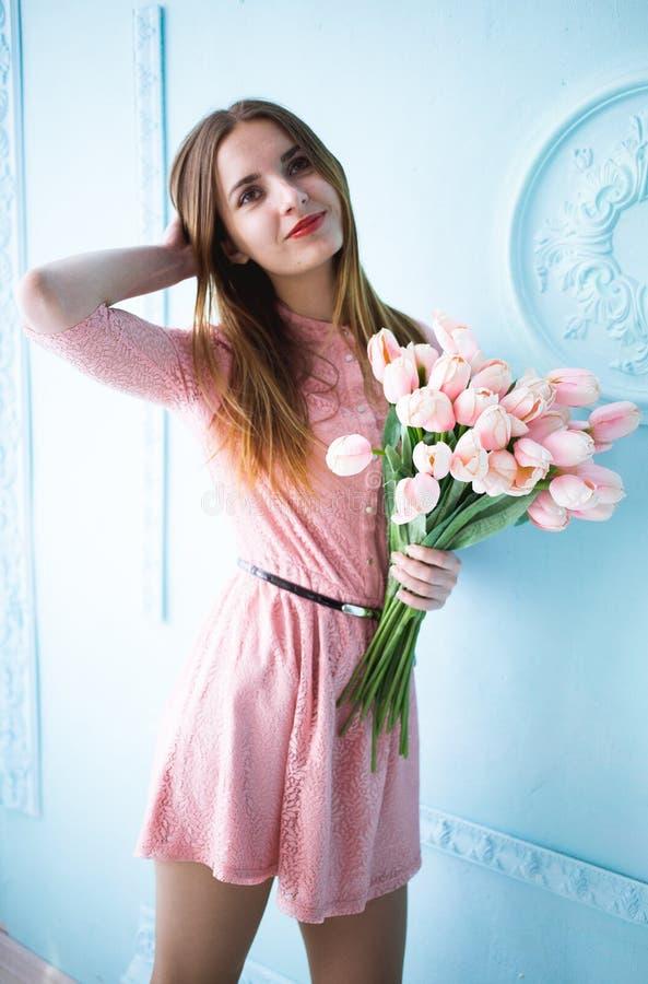 美丽的年轻女人在桃红色礼服藏品在手上反弹郁金香在蓝色墙壁背景的花花束 免版税库存照片