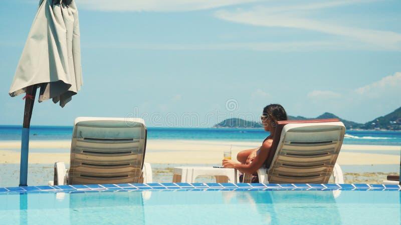 美丽的年轻女人在海滩懒人放松采取晒日光浴 库存图片