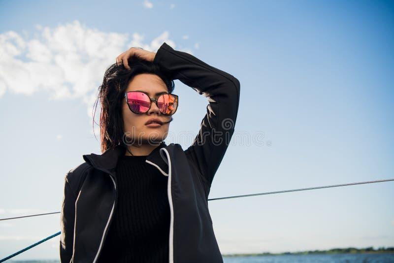 美丽的年轻女人坐游艇碗和姿势 她佩带sunglusses用手和微笑 模型在船上航行 免版税库存图片