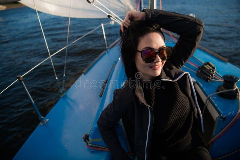 美丽的年轻女人坐游艇碗和姿势 她佩带sunglusses用手和微笑 模型在船上航行 免版税库存照片